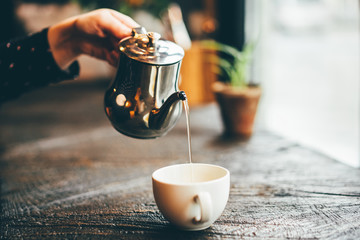 Girl pours tea from a teapot into a mug sitting in modern cafe. Close up hand with teapot. Concept of autumn mood, comfort, lifestyle, winter, cafe.