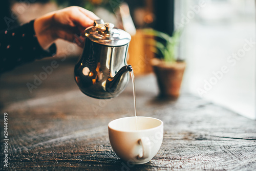 Spoed Fotobehang Thee Girl pours tea from a teapot into a mug sitting in modern cafe. Close up hand with teapot. Concept of autumn mood, comfort, lifestyle, winter, cafe.