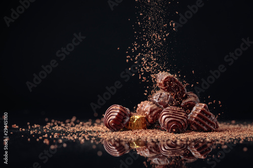 obraz lub plakat Chocolate candies on a black background sprinkled with chocolate chips.