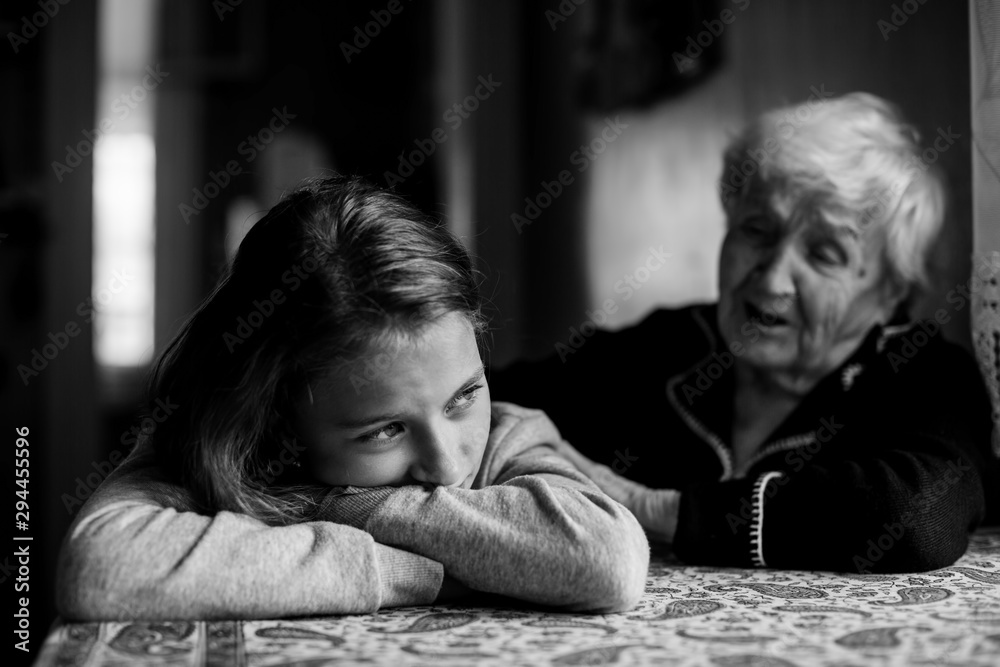 Fototapeta Little girl sad and grandmother soothes her. Black and white photo.
