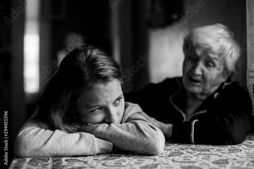 Little girl sad and grandmother soothes her. Black and white photo.