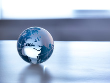 Global Markets, A Glass Globe Illustrating The World On A Desk.