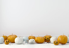 Pumpkins With Funny Faces On A White Wall Background