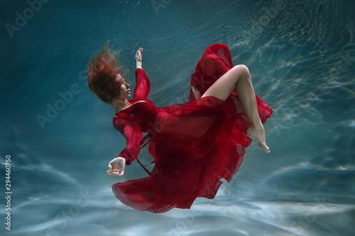 Fotografia Beautiful slender girl in a long red dress underwater.