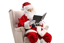 Santa Claus In An Armchair And Reading A Book