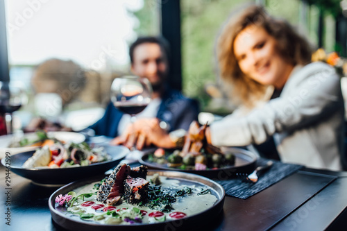 Bar Close up photo, two person eating salade and drink wine.