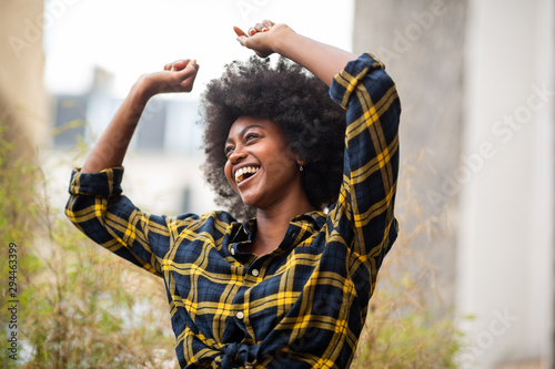 Foto cheerful young carefree afro woman with arms raised and smiling outside