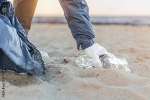 Fotomural Close up of man's hand picking up trash and plastics cleaning the beach with a g