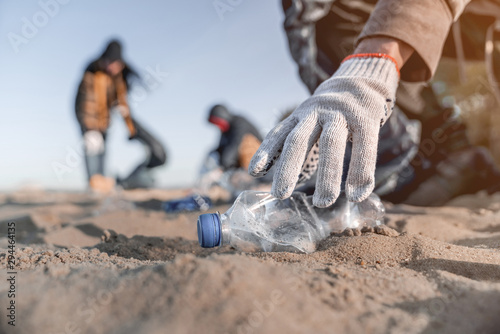Cuadros en Lienzo  Volunteer man collecting trash on the beach. Ecology concept