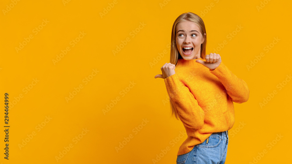 Fototapeta Cheerful cute girl pointing on copy space behing her back