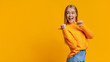 Leinwandbild Motiv Cheerful cute girl pointing on copy space behing her back