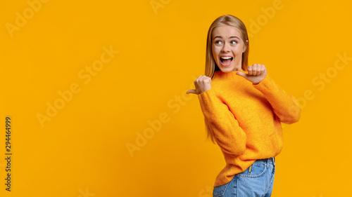 Fototapeta Cheerful cute girl pointing on copy space behing her back obraz