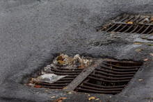Flow Of Water During Heavy Rain And Clogging Of Street Sewage. The Flow Of Water During A Strong Hurricane In Storm Sewers. Sewage Storm System Along The Road To Drain Rain Into The Drainage System