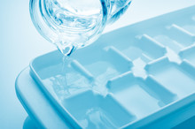 Closeup Pouring Fresh Drink Water From A Jug Into Ice Cube Tray