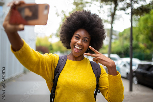 Fotografering  smiling afro american woman taking selfie with cellphone outdoors