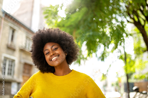 Foto  happy black girl with afro smiling outside in city