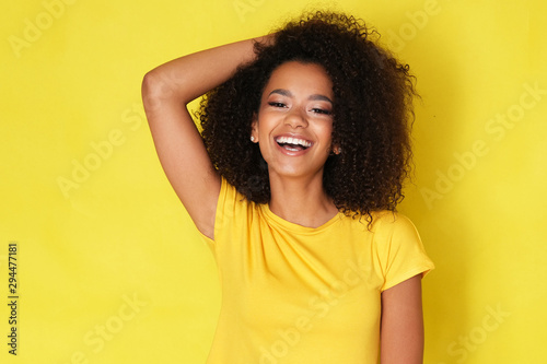 Beautiful smile from young happy model isolated on yellow background.