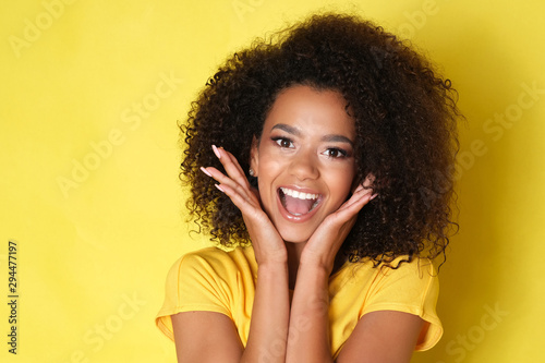 Obraz Beautiful smile from young happy model isolated on yellow background. - fototapety do salonu