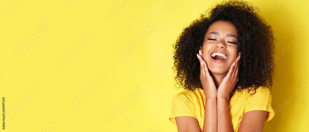 Fototapeta Super happy afro-american girl isolated on yellow background.