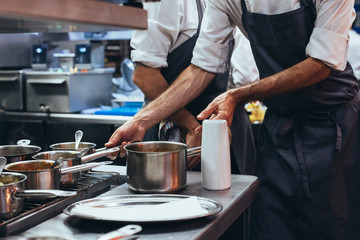 Unrecognizable chef cooking food in a restaurant kitchen