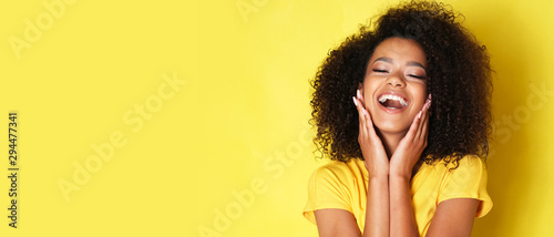 Fotografía Super happy afro-american girl isolated on yellow background.