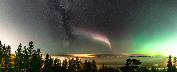 Panoramic view of Northern Lights and atmospheric phenomenon 'STEVE' meets Milky Way. Steve appears as a purple and green light ribbon in the sky at an altitude of 450 km. Northern Sweden Scandinavia