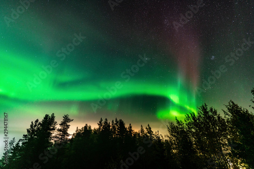Photo sur Toile Aurore polaire Northern Lights at partly clear skies with thick fog shines above Swedish foggy forest landscape in mountains, green northern lights belt curved above horizon line, Northern Sweden, Scandinavia