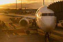 Commercial Airplane Parked At Terminal On Tarmac At Sunset