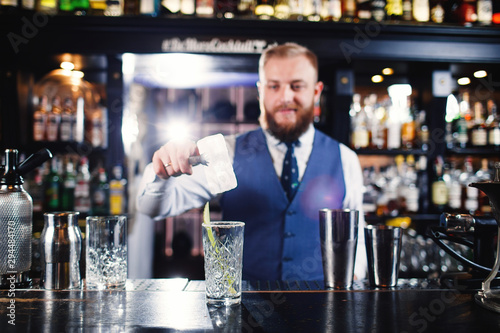 Fotografie, Obraz  Cocktail at bar. Expert Bartender is making alcoholic cocktail.