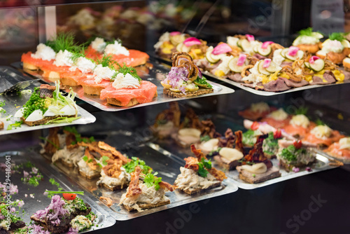 Foto auf AluDibond Natur Danish smorrebrod traditional open sandwich at Copenhagen food market store. Many sandwiches on display with seafood and meat, smoked salmon.