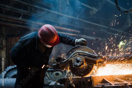 Fototapeta  Employee grinding steel with sparks - focus on grinder