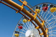 Colorful Ferris Wheel Above A Roller Coaster Track Under A Blue Sky
