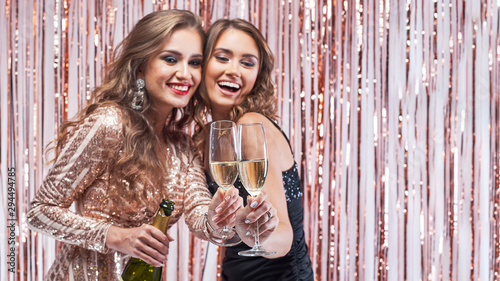 Foto  Two beautiful elegant women clinking champagne glasses.
