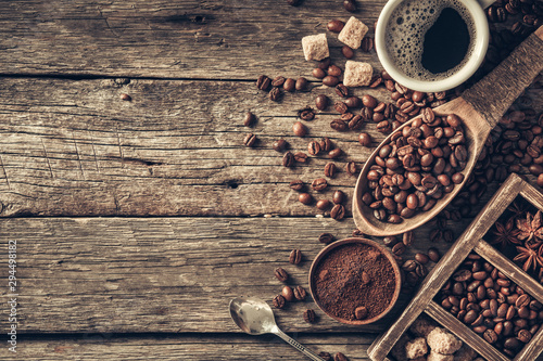 Fotografía  Coffee cup with coffee beans on wood background.