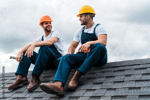 happy handymen in helmets and uniform sitting on rooftop