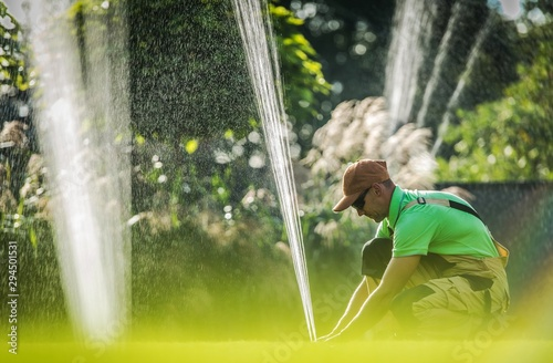 Photo Worker Adjusting Water Sprinkler