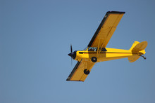 Airplane With Propeller Flying In Blue Sky