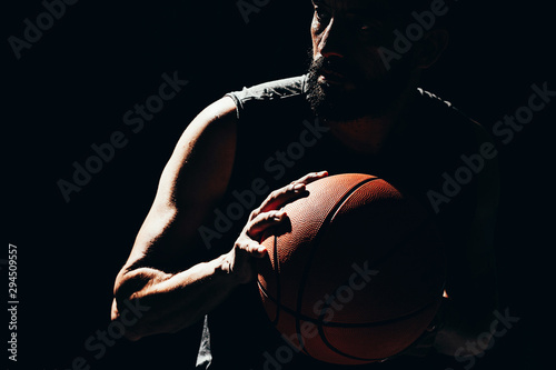 Foto Dramatic portrait of basketball player over dark background