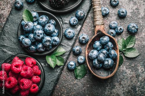 Fresh berries with raspberries, blueberries, blackberries in bowl on a stone stand on a dark metal background. - 294511334