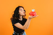Leinwanddruck Bild - Happy Asian woman with piggy bank on color background