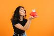 Leinwandbild Motiv Happy Asian woman with piggy bank on color background