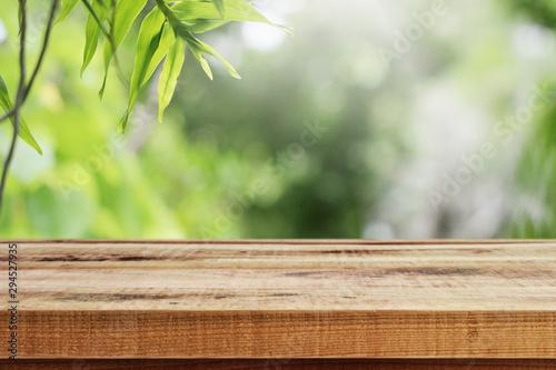 Fotobehang Lente Wooden desk and green leaf nature in garden background.