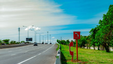 Emergency SOS Telephone Installed At Roadside. Highway SOS Call Box. Motorway Emergency Roadside Call System. Emergency Phone For Help People Had Car Accident On Highway. Car Driving On Asphalt Road.