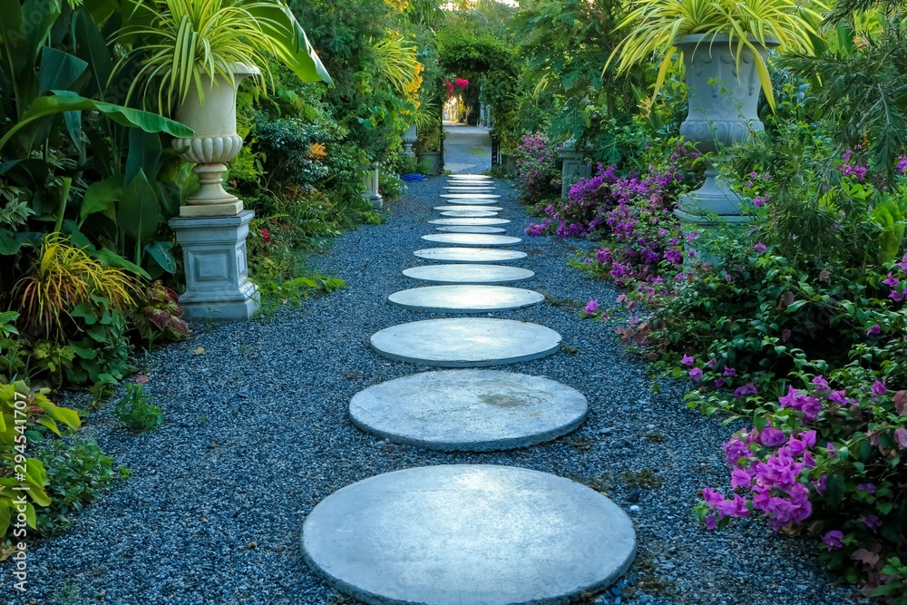 Fototapety, obrazy: Circular concrete path in botanical tropical garden, Colorful green leaves and blooming flowers around walkway.