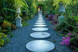 Circular concrete path in botanical tropical garden, Colorful green leaves and blooming flowers around walkway.