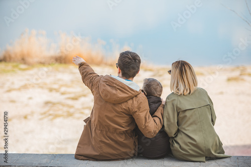 Fotografiet  young beautiful family sitting at beach with view lake