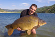 canvas print picture - Carp fishing, man holding a big common carp. France