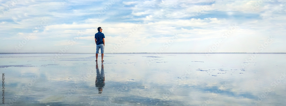 Fototapeta man in the water at sea. concept of a happy holiday and freedom. tourist looking at the horizon line. Beautiful panorama of the salt lake with the reflection of white clouds in the ode.