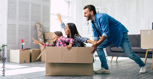 Fototapeta Little girl is riding in a cardboard box and pointing straight ahead while her mother imitates a plane and laughs, and father is pushing the box, enjoying their time together in their new house. obraz