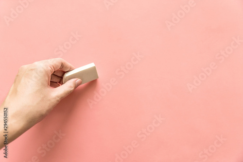 Fotografía  Hand holding white rubber for erasing something on empty pink background